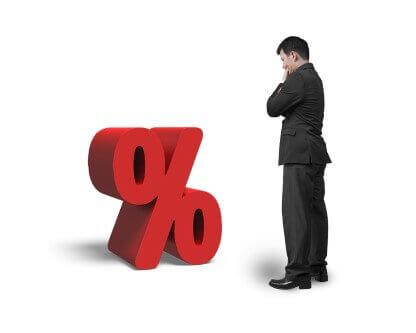אדם בחליפה עומד מול סימן אחוז גדול שמסמל ריבית של משכנתא