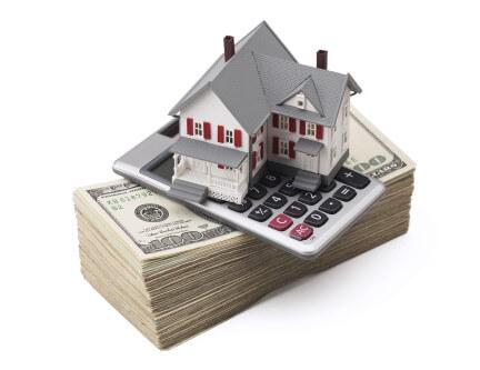 דגם של בית ומחשבון על ערמה של כסף