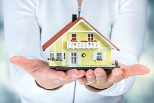 אשה מחזיקה דגם של בית בידיים