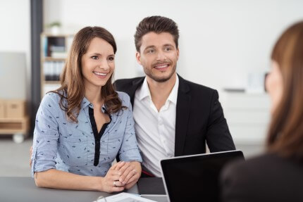זוג יושב מול יועצת משכנתא בפגישה