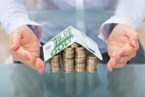 אדם מניח את הידיים מסיב לדגם של בית שעשוי ממטבעות ושטרות