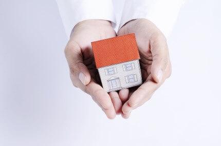 דגם קטן של בית בתוך כפות ידיים