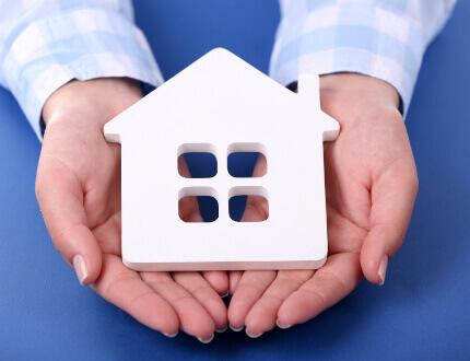 כפות ידיים אוחזות בדגם לבן של בית